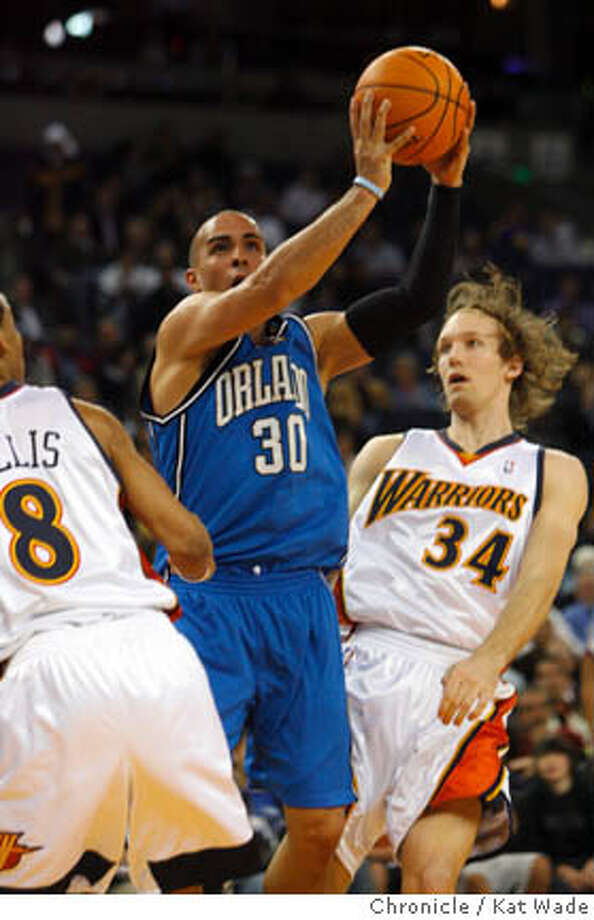 _O0R2045.JPG  The Orlando Magic's #30 Carlos Arroyo drives past the Golden State Warrior's #8 Monta Ellis and #34 Mike Dunleavy to make a basket during the fourth quarter of the game against the Orlando Magic at the Oracle Arena on Wednesday night January 10, 2007. The Warriors lost 76 to 91. Kat Wade/The Chronicle Mandatory Credit for San Francisco Chronicle and photographer, Kat Wade, Mags out Photo: Kat Wade