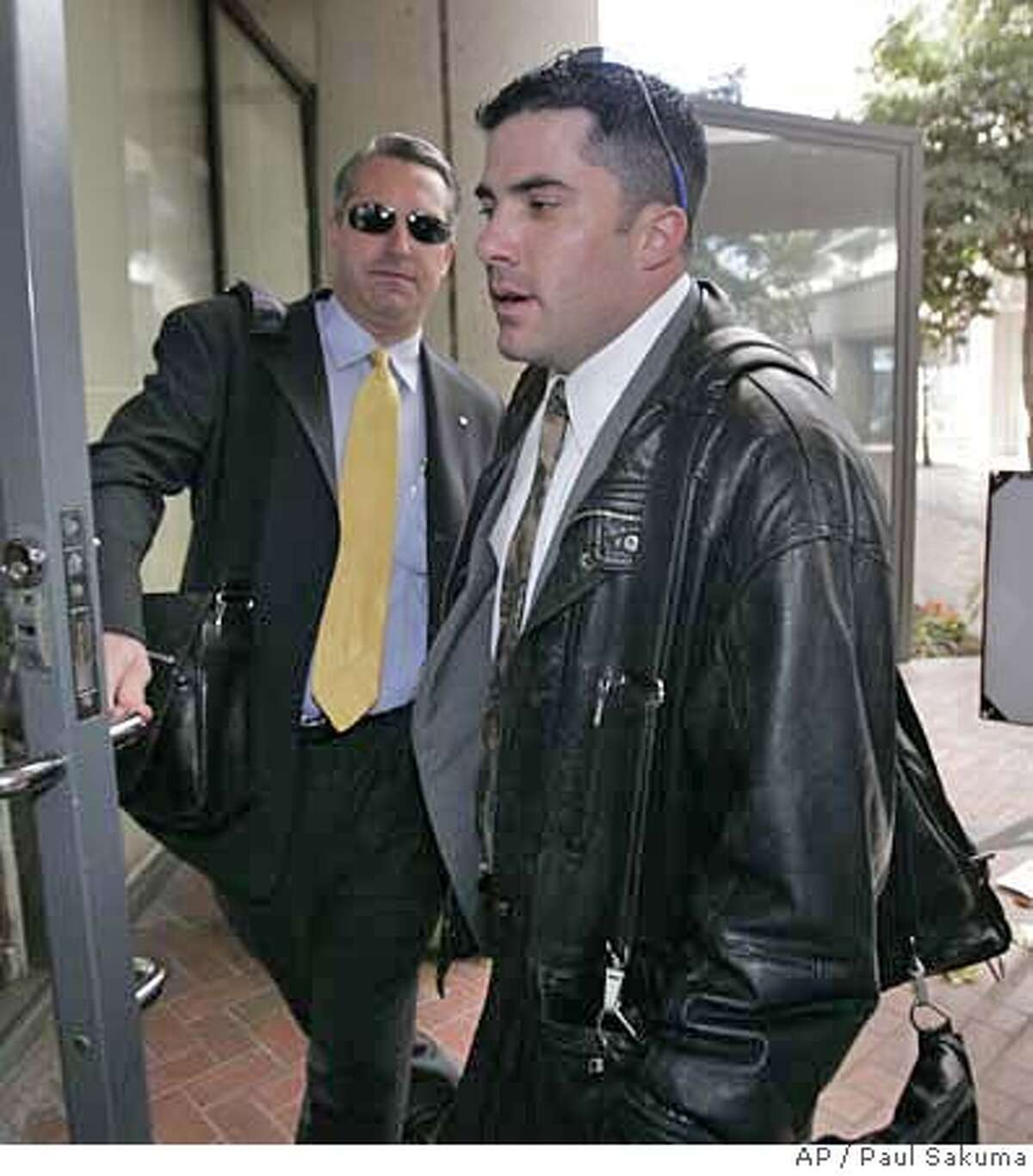 Bryan Wagner , right,of Littleton, Colorado, re-enters a federal courthouse, with his attorney, left, in San Jose, Calif., Friday, Jan. 12, 2007 after he plead guilty to two counts of conspiracy and identity theft. Wagner, a private investigator, was apparently at the bottom of a long chain of command involved in the probe that reached into Hewlett Packard's top ranks. (AP Photo/Paul Sakuma)