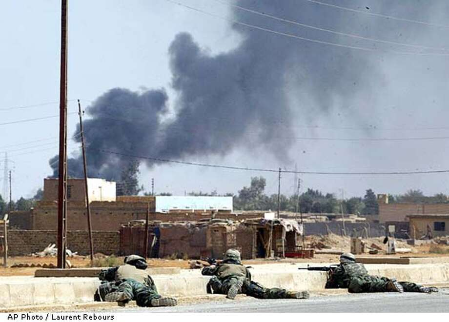 US Marines take cover during a fierce battle with Iraqi troops inside the town of Kut, central Iraq, Thursday, April 3, 2003. (AP Photo / Laurent Rebours) Photo: LAURENT REBOURS