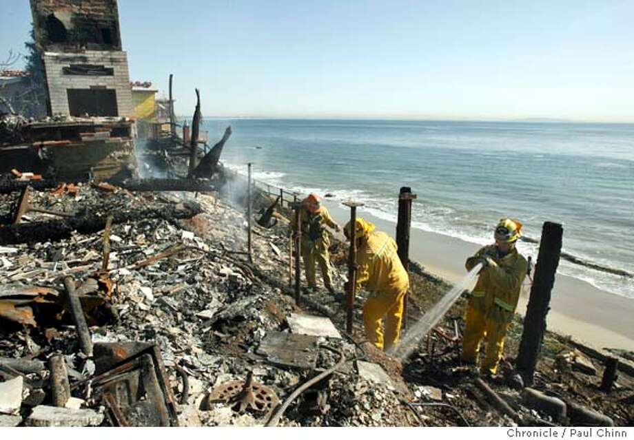 Firefighters doused hot spots on one of four beachfront homes in Malibu, Calif. on Tuesday, Jan. 9, 2007. A huge brush fire, fanned by unseasonal Santa Ana winds, raced down a hillside Monday evening quickly gutting the four multi-million dollar homes and damaging several others.  PAUL CHINN/The Chronicle  Ran on: 01-10-2007  Firefighters douse hot spots on one of five Malibu beachfront homes ravaged by a fast-moving wildfire.  Ran on: 01-10-2007  Firefighters douse hot spots on one of five Malibu beachfront homes ravaged by a fast-moving wildfire that was fueled by dense brush.  Ran on: 01-10-2007 Ran on: 01-10-2007  Firefighters douse hot spots on one of five Malibu beachfront homes ravaged by a fast-moving wildfire. Photo: PAUL CHINN