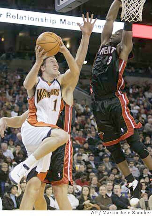 Golden State Warriors' Troy Murphy, left, goes up for a shot while defended by Miami Heat's Dwyane Wade, right, during the second half of an NBA basketball game in Oakland, Calif., Friday, Jan. 12, 2007. (AP Photo/Marcio Jose Sanchez) EFE OUT Photo: Marcio Jose Sanchez