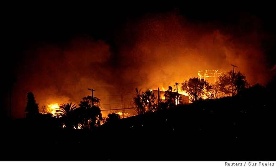 The Malibu coastline glows as a million dollar home burns in Malibu January 8, 2007. The wind-driven wildfire burned out of control near the seaside California community of Malibu on Monday, destroying eight homes and damaging five others. REUTERS/Gus Ruelas (UNITED STATES) Photo: GUS RUELAS
