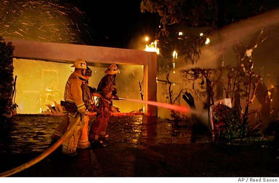 Firefighters train water on a burning home as gusting winds blow embers on Malibu Road Monday, Jan. 8, 2007. A wildfire fanned by Santa Ana winds destroyed eight seaside mansions and damaged five others as it spread over more than 20 acres in this celebrity enclave Monday, authorities said. (AP Photo/Reed Saxon) Photo: Reed Saxon
