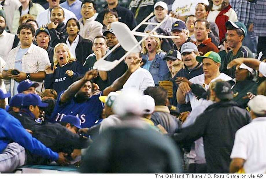 Texas Rangers reliever Frank Francisco, bottom left, hurls a ballboy's chair into the crowd of Oakland Athletics fans during a melee that erupted in the ninth inning, Monday, Sept. 13, 2004 in Oakland, Calif. A woman was hit in the face and injured in the fracas, and Francisco was arrested. The A's won 7-6 in 10 innings. (AP Photo/The Oakland Tribune, D. Ross Cameron) Photo: D. ROSS CAMERON