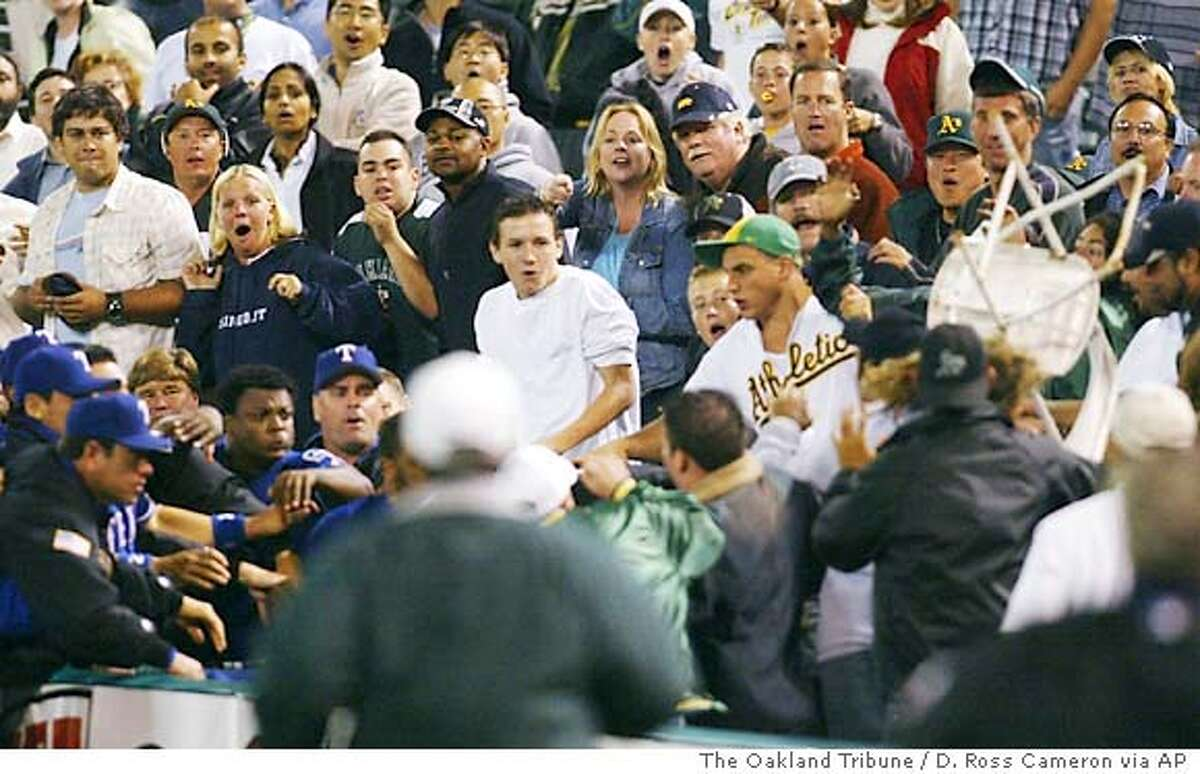 Oakland Athletics fans react as a chair, thrown by Texas Rangers reliever Frank Francisco, bottom left without a hat, flies into the crowd during a brawl in the ninth inning, Monday, Sept. 13, 2004 in Oakland, Calif. An unidentified woman (seen on the right being hit by the chair) was struck in the face and injured by the chair, and Francisco was arrested and charged with assault. The fracas delayed the game for 19 minutes. When order was restored, the A's won the game, 7-6, in 10 innings. (AP Photo/The Oakland Tribune, D. Ross Cameron)