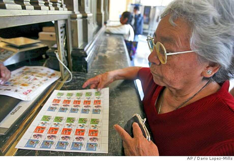 "An unidentified woman buys a full sheet of postage stamps of a series of five stamps depicting ""Memin Pinguin,"" a black cartoon character with exaggerated features from a comic book started in 1945 at the main postal office in Mexico City, Mexico, on Thursday, June 30, 2005. The stamps, which have sold briskly on the first day of their sale to the general public, have stirred criticism in the United States charging they are racist and offensive.(AP Photo/Dario Lopez-Mills)**EFE OUT** Photo: DARIO LOPEZ-MILLS"