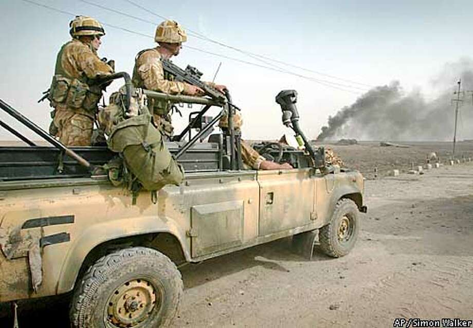 British Royal Marines in Abu al Khasib, a southern suburb of Basra, Monday March 31, 2003, where 40 Commando Royal Marines fought a pitched battle with Iraqi forces. The commandos destroyed Iraqi tanks and seized equipment.(AP Photo/Simon Walker,London Times, Pool) Photo: SIMON WALKER