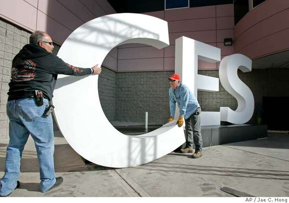 Deano Aliotta, left, and John Day install a sign for the Consumer Electronics Show at the entrance of Las Vegas Convention Center in Las Vegas on Wednesday, Jan. 3, 2007. With 2,700 exhibitors, the largest technology trade show in the world takes place in Las Vegas from Jan. 8 to Jan. 11. About 150,000 attendees are expected at this year's CES. (AP Photo/Jae C. Hong) Photo: JAE C. HONG