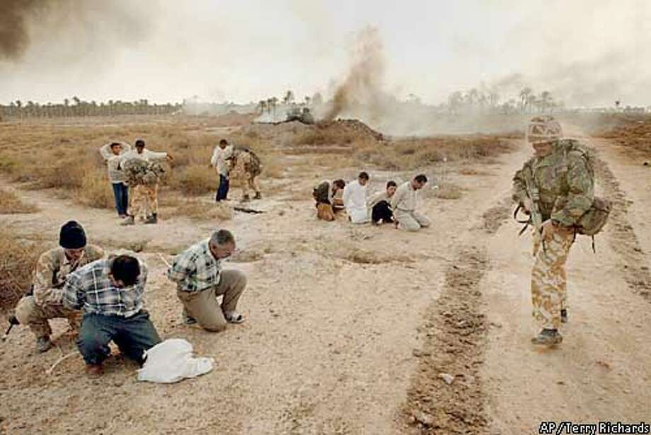 Iraqi militia surrender as 40 Commando Royal Marines move into Abu Al Khasib, a suburb of Basra in southern Iraq Sunday, March 30, 2003. (AP Photo/Terry Richards, Pool) Photo: TERRY RICHARDS.