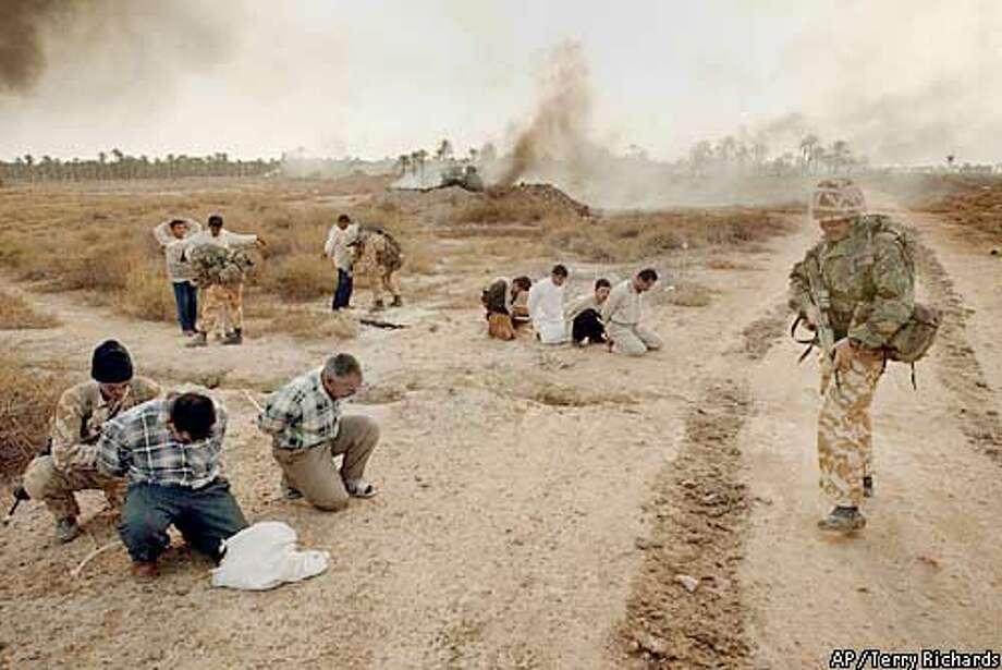 Iraqi militia surrender as 40 Commando Royal Marines move into Abu Al Khasib, a suburb of Basra in southern Iraq Sunday, March 30, 2003. (AP Photo/Terry Richards, Pool) Photo: TERRY RICHARDS.