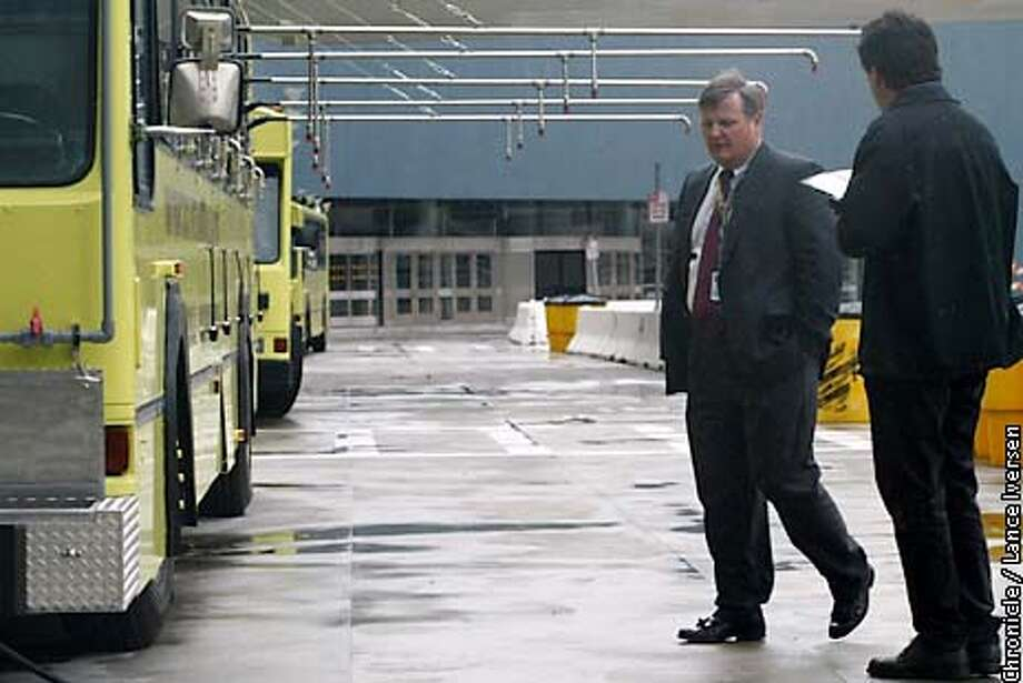 SFO spokesman Michael McCarron (left ) shows off the new mobile decontamination busses shower heads to a member of the media yesterday.BY LANCE IVERSEN/SAN FRANCISCO CHRONICLE/ED NOTE COLOR PHOTO IS NOT CORRECTED Photo: LANCE IVERSEN