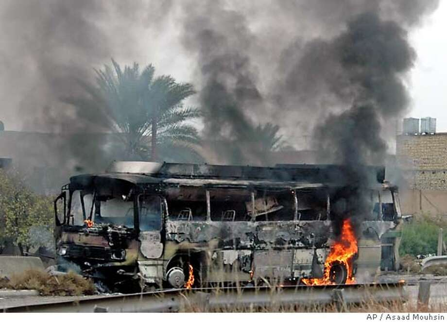 A bus destroyed in an ambush stands on the side of the road in Baghdad, Iraq, Monday, Jan. 8, 2007. Unknown gunmen attacked a bus full of mainly Shiite workers from Baghdad's Sadr City neighborhood en route to the airport, killing 9 persons and wounding at least 11, a hospital paramedic said. (AP Photo/Asaad Mouhsin) Photo: ASAAD MOUHSIN