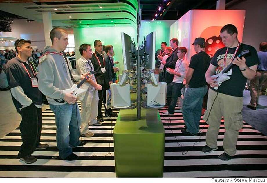 """Attendees try out """"Guitar Hero II"""", a game for the Xbox video game system, at the Microsoft booth during the 2007 International Consumer Electronics Show (CES) in Las Vegas, Nevada January 8, 2007. REUTERS/Steve Marcus (UNITED STATES) Photo: STEVE MARCUS"""