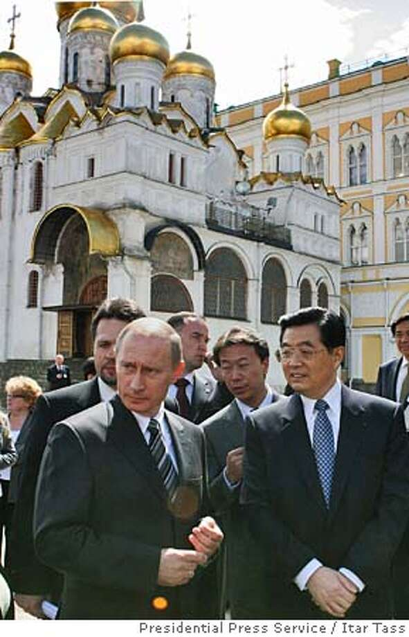 Russian President Vladimir Putin, left, and Chinese President Hu Jintao tour the Cathedral Square, with the Annuciation Cathedral in the background, in the Kremlin in Moscow, Friday, July 1, 2005. The presidents of Russia and China warned other nations on Friday against attempts to dominate global affairs and interfere in the domestic issues of sovereign nations in what appeared to be a veiled expression of their irritation with U.S. policy. (AP Photo/ITAR-TASS, Presidential Press Service) Photo: ITAR TASS
