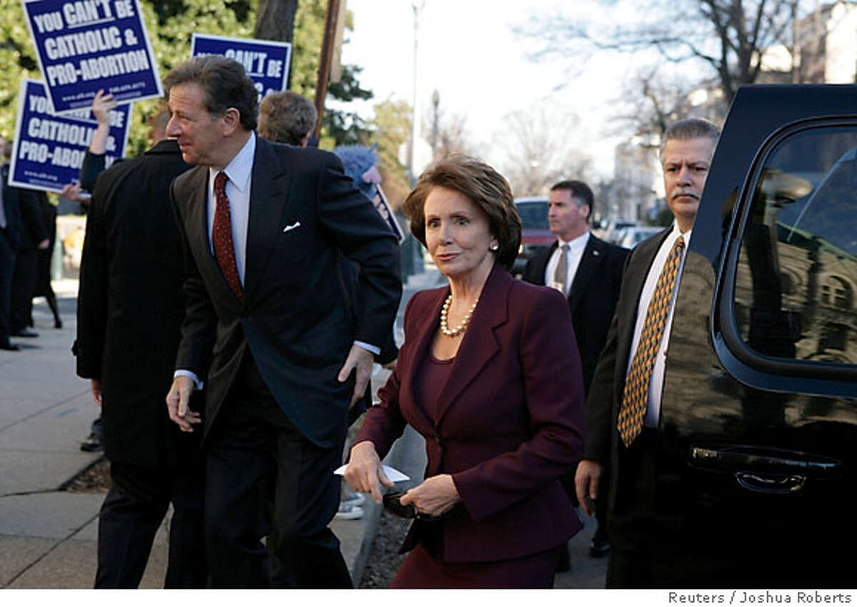 U.S. Speaker of the House elect Nancy Pelosi and her husband Paul walk past abortion protesters as they arrive for an interfaith prayer service for House leadership at St. Peter's Catholic Church in Washington January 4, 2007. REUTERS/Joshua Roberts (UNITED STATES)