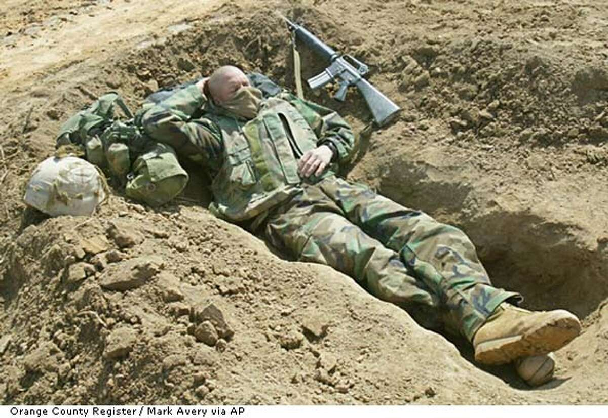 Staff Sgt., Allen Tipps of Sparks, Nev., takes a nap in his skirmish hole at the 1st Battalion-5th Marine Division encampment, Friday, March 28, 2003, in Iraq. Orange County Register / Mark Avery