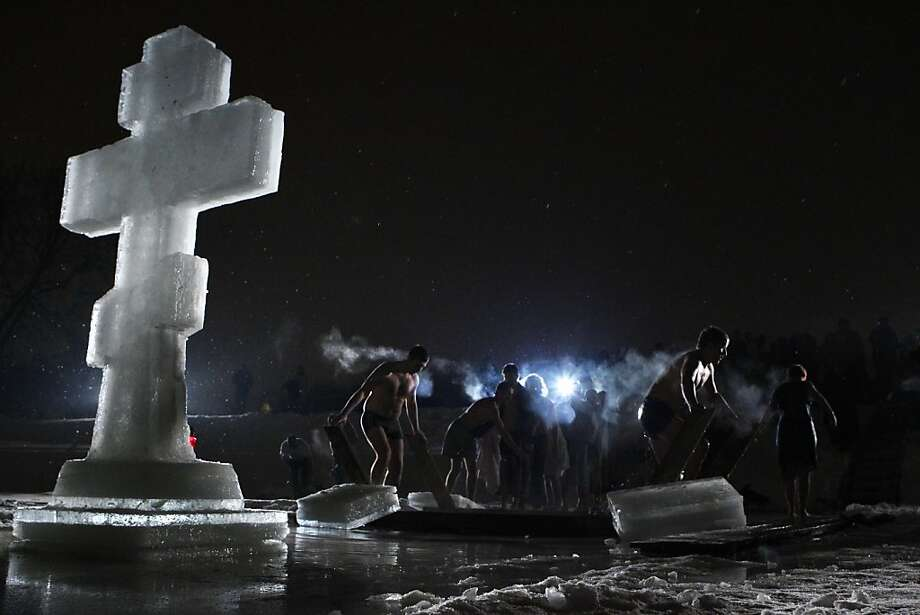 People gather around a bath of ice cold water as they prepare to plunge into it at the Kolomenskoe park on the outskirts of Moscow, Russia, Thursday, Jan. 19, 2012. Thousands of Russian Orthodox Church followers plunged into icy rivers and ponds across the country to mark Epiphany, during which they cleanse themselves with water deemed holy for the day. Water that is blessed by a cleric on Epiphany is considered holy and pure until next year's celebration, and is believed to have special powers of protection and healing. (AP Photo/Mikhail Metzel) Photo: Mikhail Metzel, Associated Press
