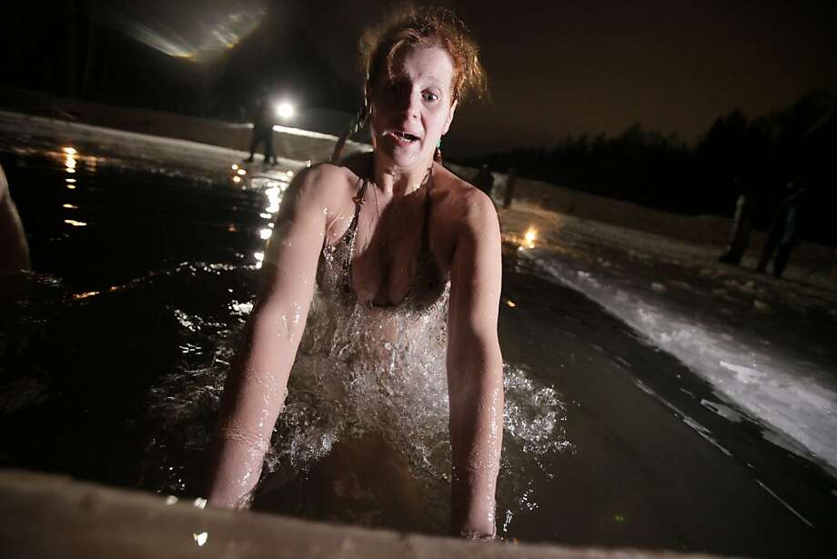 A Russian woman emerges from the icy water on Epiphany at a pond in Tyarlevo village outside St. Petersburg, Russia, early Thursday, Jan. 19, 2012. Thousands of Russian Orthodox Church followers plunged into icy rivers and ponds across the country to mark Epiphany, during which they cleanse themselves with water deemed holy for the day. Water that is blessed by a cleric on Epiphany is considered holy and pure until next year's celebration, and is believed to have special powers of protection and healing.(AP Photo/Dmitry Lovetsky) Photo: Dmitry Lovetsky, Associated Press