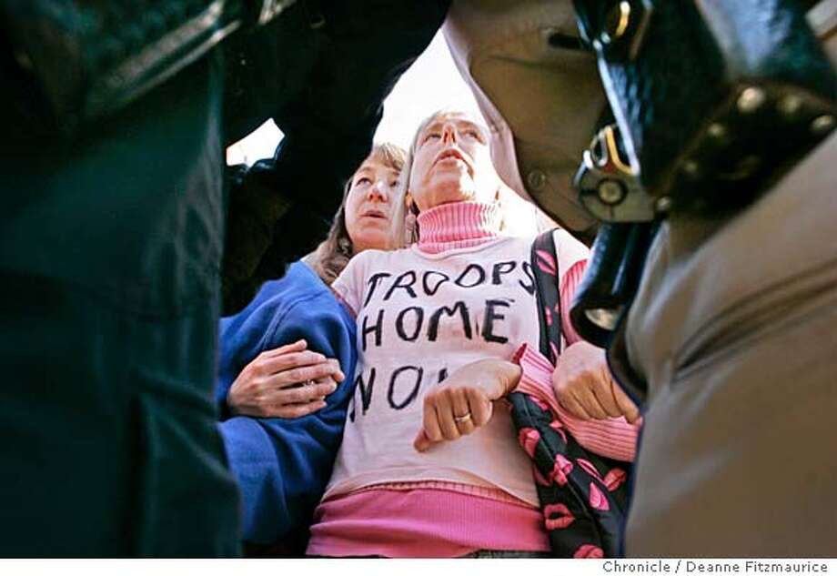 CORRECTS YEAR TO 2007 STED 2006 ** Leslie Angelina, center left, and Medea Benjamin, with anti-war group CODEPINK, join arms with others before they were taken into custody by police during a demonstration marking the 3,000th death of American military personnel in Iraq, Monday, Jan. 1, 2007, in San Francisco. The rally, organized by CODEPINK, included a shutdown of the Golden Gate Bridge to pedestrians and cyclists for hours. (AP Photo/The San Francisco Chronicle, Deanne Fitzmaurice) ** MANDATORY CREDIT, MAGS OUT, Photo: Deanne Fitzmaurice