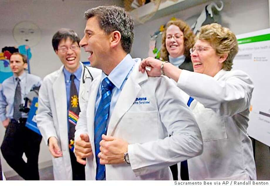 Dr. Claire Pomeroy, right, vice chancellor for Human Health Sciences at UC Davis and dean of the UC Davis School of Medicine, helps Assembly Speaker Fabian Nunez put on a white lab coat following a news conference at UC Davis Pediatrics General Clinic in Sacramento, Calif., on Thursday, Dec. 21, 2006. Nunez discussed a proposed health care plan to insure all Californians. (AP Photo/Sacramento Bee, Randall Benton) ** MAGS OUT TV OUT ONLINES OUT ** MAGS OUT TV OUT ONLINES OUT Photo: Randall Benton
