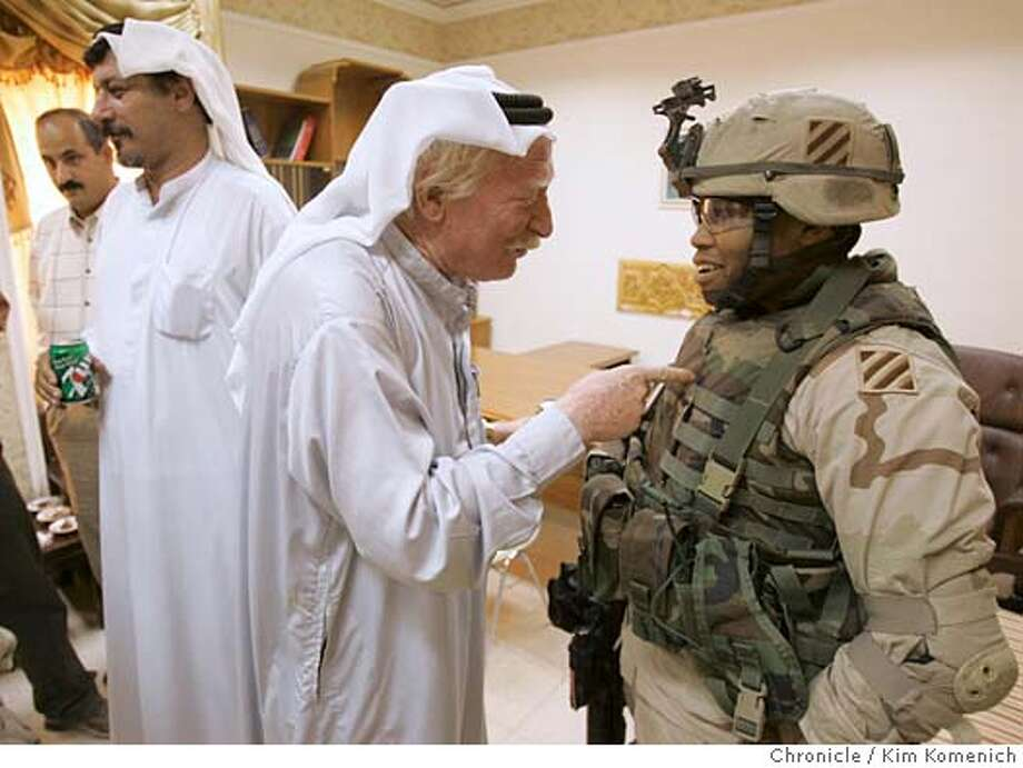 After a meeting spent hiring new hospital employees, Sheikh Ahmed Fahad Al Hazza, center, jokes with U.S. Army Lt. Ashley Garry (right, of Black platoon, Charlie company, 2-7 Infantry Battalion, 1st Brigade, 3rd Infantry.) He is the Army's liason to the Ajua area. Man at far left is not identified. Man second from left is Sheikh Thaad Al Hazza.  We visit Auja Village (pop. 5,000, the hometown of Saddam Hussein. We visit a hospital that was originally built for Saddam and his family which is scheduled to open as a public hospital on June 26.  San Francisco Chronicle photo by Kim Komenich Photo: Kim Komenich