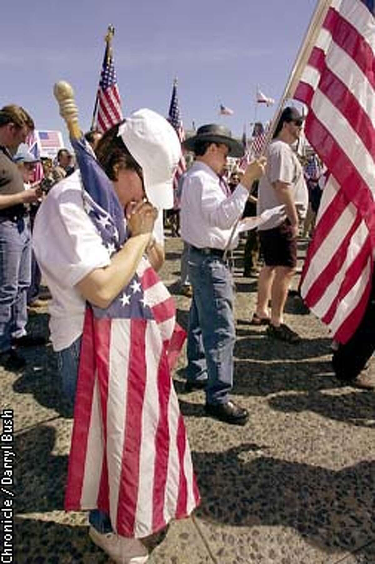 Barbara Mecham of San Carlos, prays while holding an American flag along with others attending a pro-troops rally held at Civic Center in San Francisco. Chronicle Photo by Darryl Bush