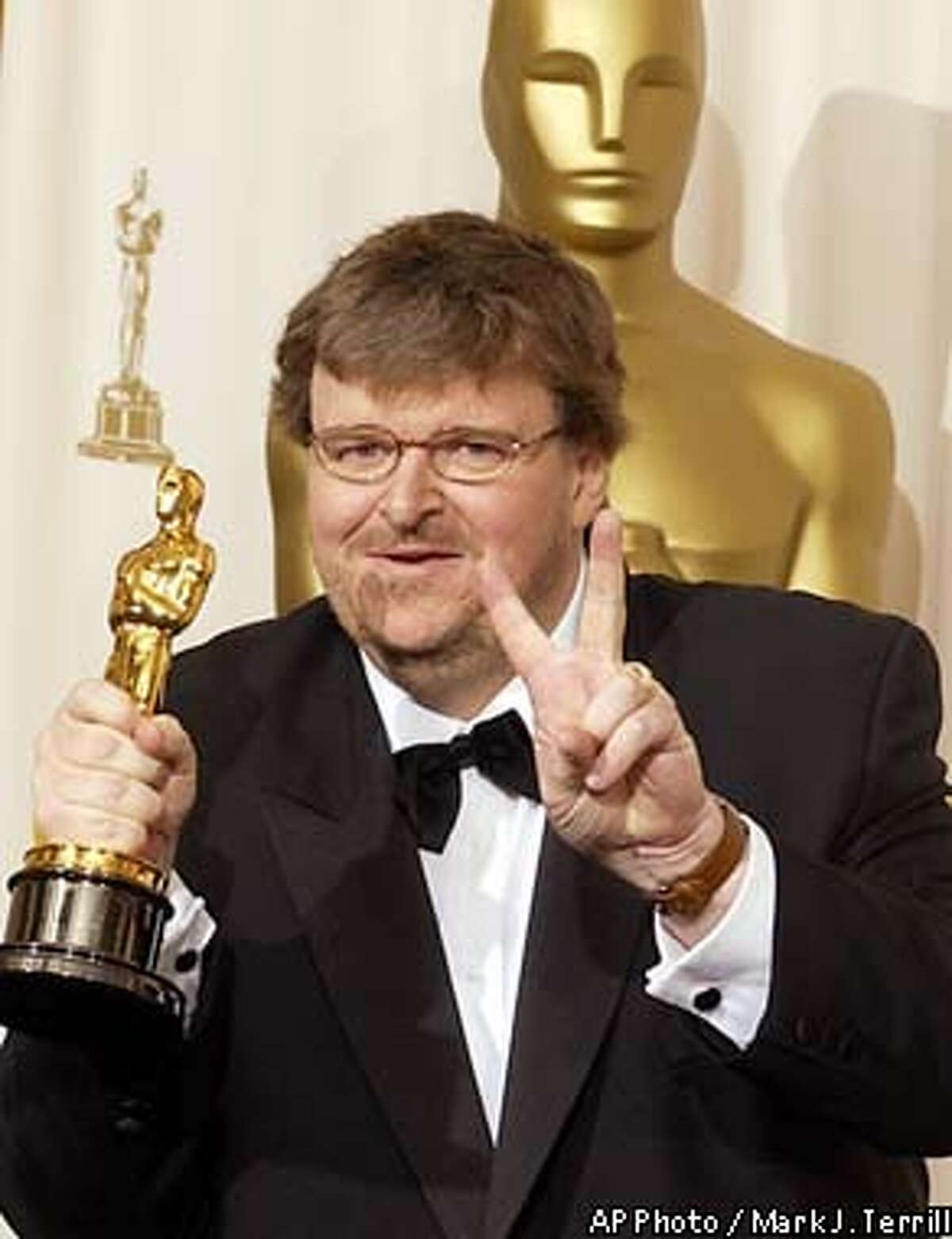 ** EMBARGOED AT THE REQUEST OF THE MOTION PICTURE ACADEMY FOR USE UPON CONCLUSION OF ACADEMY AWARDS TELECAST ** Michael Moore flashes the peace sign as he poses with the won for best documentary feature for the film