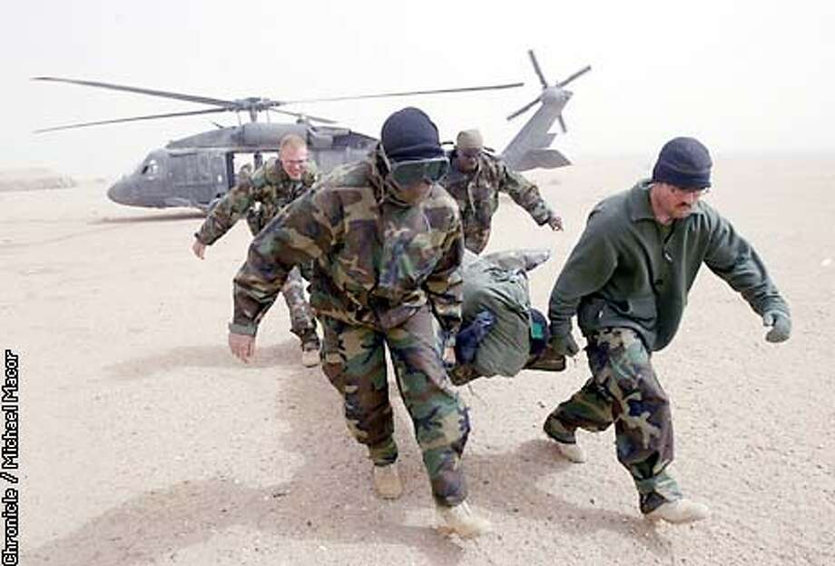 Medical personell carry an injured Marine to a waiting ambulance after being flown out of Central Iraq by Blackhawk Helicopter. The Marine is expected to recovery from non life threatening injuries. Camp Viper, Western iraq Desert. by Michael Macor/The Chronicle Photo: MICHAELMACOR