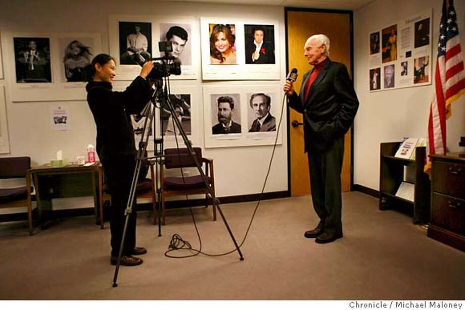 Congressman Tom Lantos is video taped by Ning Han (left), a reporter for New Tang Dynasty Television. Every year he is taped welcoming the viewers of the chinese language broadcast station to the chinese lunar new year. On the walls of the reception area of his office are portraits of other Hungarians, an exhibit titled 'A Celebration of Gifted Hungarians'.  Congressman Tom Lantos, the veteran San Mateo lawmaker is about to become chair of the House International Relations committee. Lantos was photographed in his San Mateo congressional district office on Wednesday, 20 December, 2006.  Photo by Michael Maloney / San Francisco Chronicle MANDATORY CREDIT FOR PHOTOG AND SF CHRONICLE/ -MAGS OUT Photo: Michael Maloney