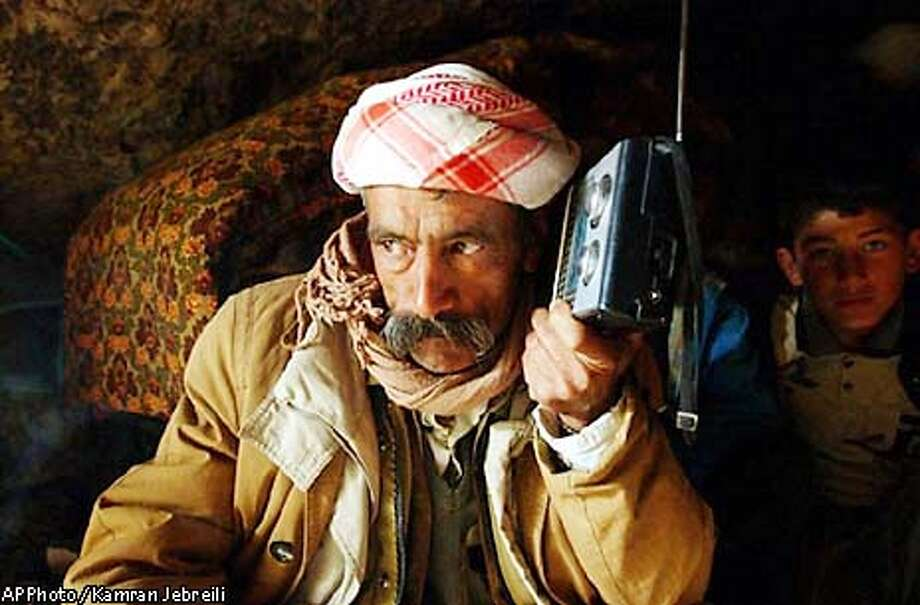** RETRANSMISSION OF XKJ107 FOR ALTERNATE CROP ** Iraqi-Kurd Khamoo Haji, 52, listens to a radio as he takes shelter inside a cave about 10 kilometers (6 miles) south of Dohuk, in Kurdish-controlled northern Iraq, Tuesday, March 25, 2003. Coalition warplanes landed in Kurdish territory Monday and launched airstrikes against barracks in northern Iraq, prompting frightened residents to flee the area. (AP Photo / Kamran Jebreili) Photo: KAMRAN JEBREILI
