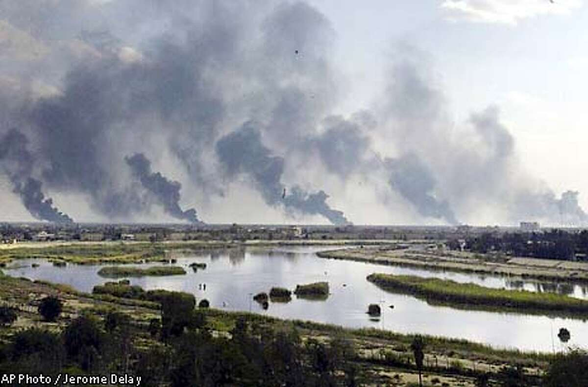 ** RETRANSMISSION TO PROVIDE ALTERNATE CROP ** Columns of smoke rise in the horizon of Iraq's capital city Baghdad Saturday March 22, 2003 following US-led forces bombardments. (AP Photo/Jerome Delay)