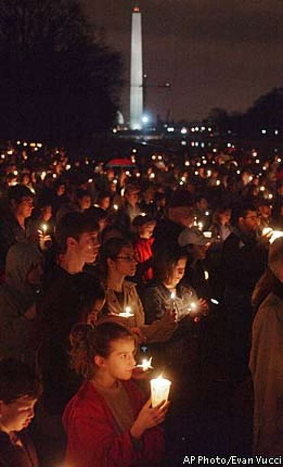 With the Washington Monument in the background, ten-year-old Emilia Morrow, of Rockville, Md., holds a candle as she participates in a candlelight vigil at the Lincoln Memorial Sunday, March 16, 2003 in Washington. Several hundred demonstrators opposing a seemingly imminent war with Iraq gathered at the base of the memorial in a protest sponsored by Win Without War and MoveOn.org. (AP Photo/Evan Vucci) Photo: EVAN VUCCI