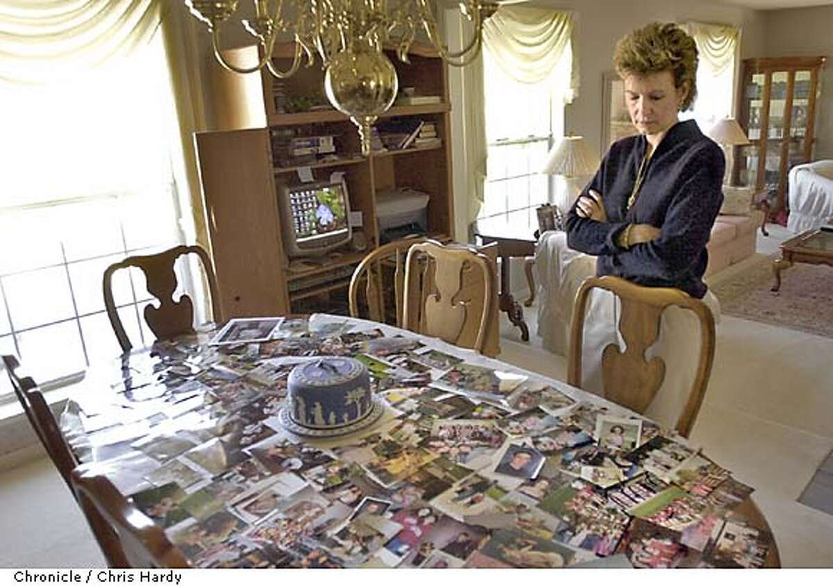 CHRISTINE MCFADDEN, WHOSE CHILDREN WERE KILLED BY HER EX HUSBAND, LOOKING AT PHOTOS OF HER KIDS SPREAD OUT ON HER DININGROOM TABLE -----CHRONICLE PHOTO BY CHRIS HARDY