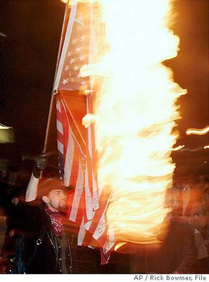 ** FILE ** A protester burns an American flag to protest President Bush's second inauguration during a march in downtown Portland, Ore., in this Thursday, Jan. 20, 2005 file photo. The House on Wednesday, June 22, 2005 approved a constitutional amendment that would give Congress the power to ban desecration of the American flag, a measure that for the first time stands a chance of passing the Senate as well. (AP Photo/Rick Bowmer) Photo: RICK BOWMER