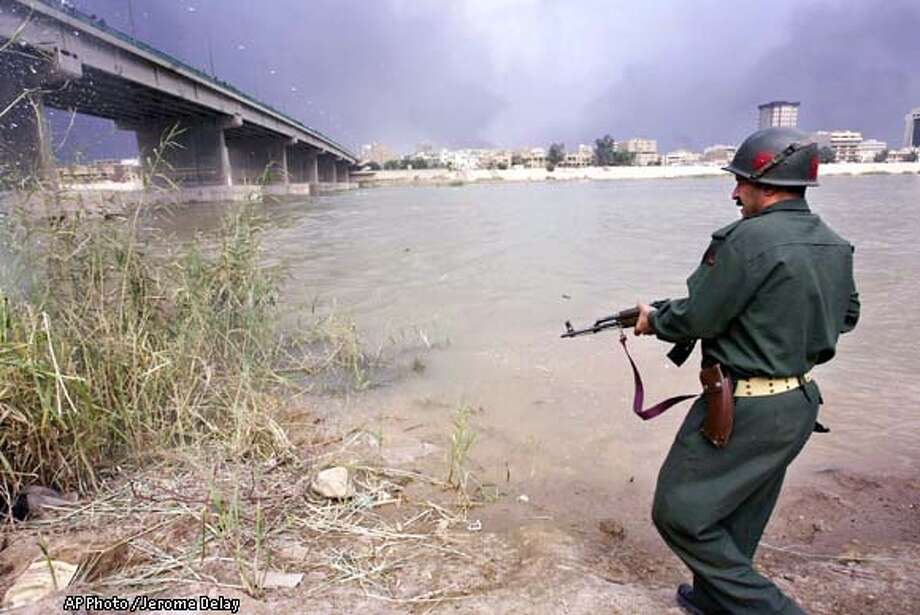An Iraqi soldier fires his gun into sugar cane on the banks of the Tigris River Sunday, March 23, 2003, as Iraqi police and security agents searched for a possibly downed coalition pilot. The U.S. Central Command in Qatar and the Pentagon said there were no reports of any coalition aircraft being shot down or a pilot being missing. (AP Photo/Jerome Delay) Photo: JEROME DELAY