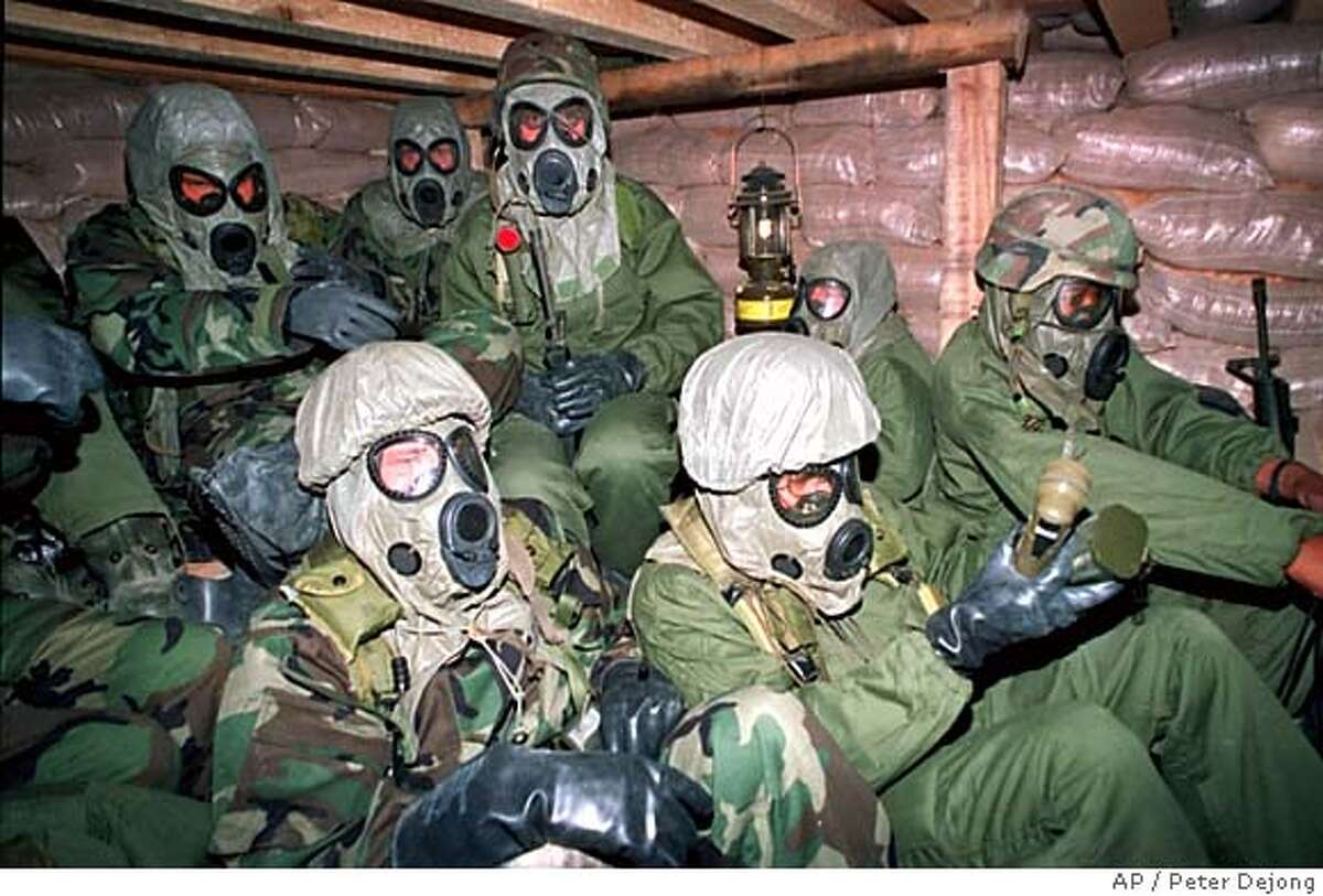 FILE--Soldiers with the U.S. army's 7th Corps huddle in a bunker in Eastern Saudi Arabia with gas masks and chemical suits just after U.S. planes started bombing Iraq in Jan. 18, 1991. (AP Photo/ Peter Dejong, Pool)