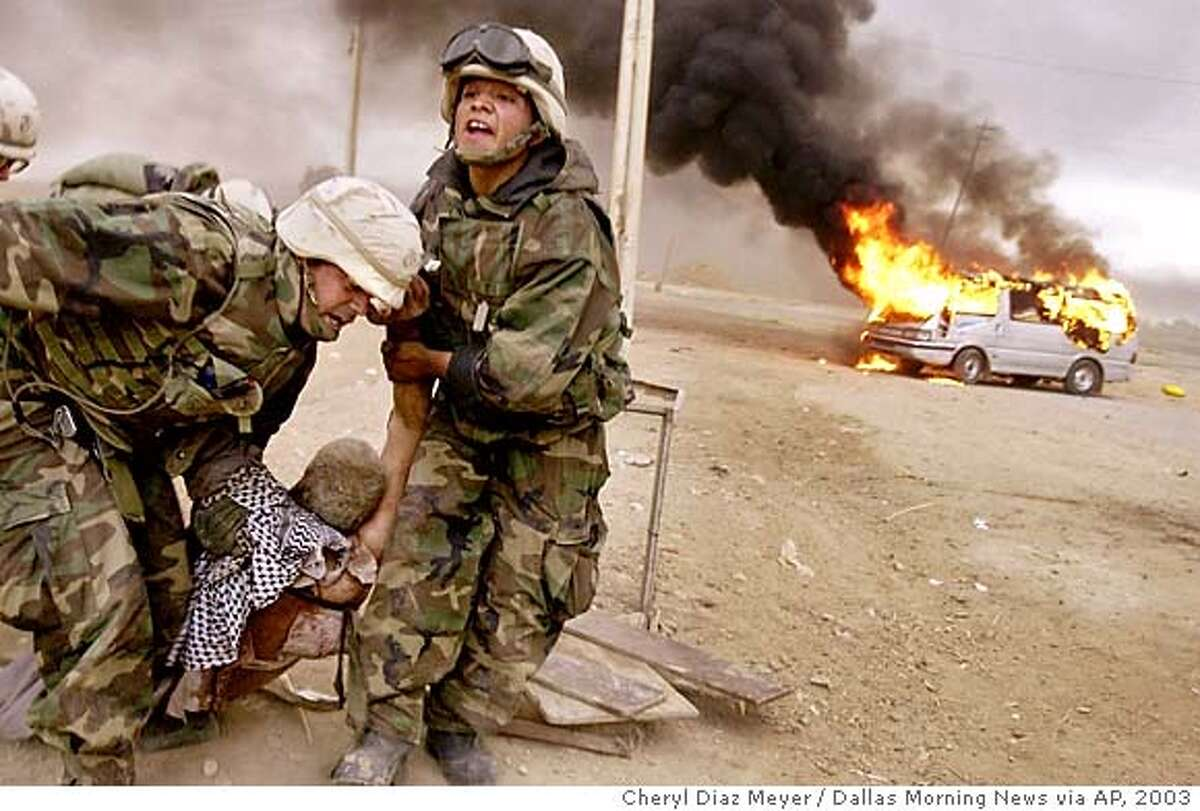 Lt. Jeffrey Goodman, left, and Lance Cpl. Jorge Sanchez, drag a wounded civilian away from his burning vehicle during an advance on Baghdad by the 2nd Tank Battalion Friday, April 4, 2003. The man was injured when he raced into the midst of a battle. (AP Photo, Cheryl Diaz Meyer, Dallas Morning News) CAT MANDATORY CREDIT, FORT WORTH OUT, , NO MAGS, TV OUT, INTERNET OUT