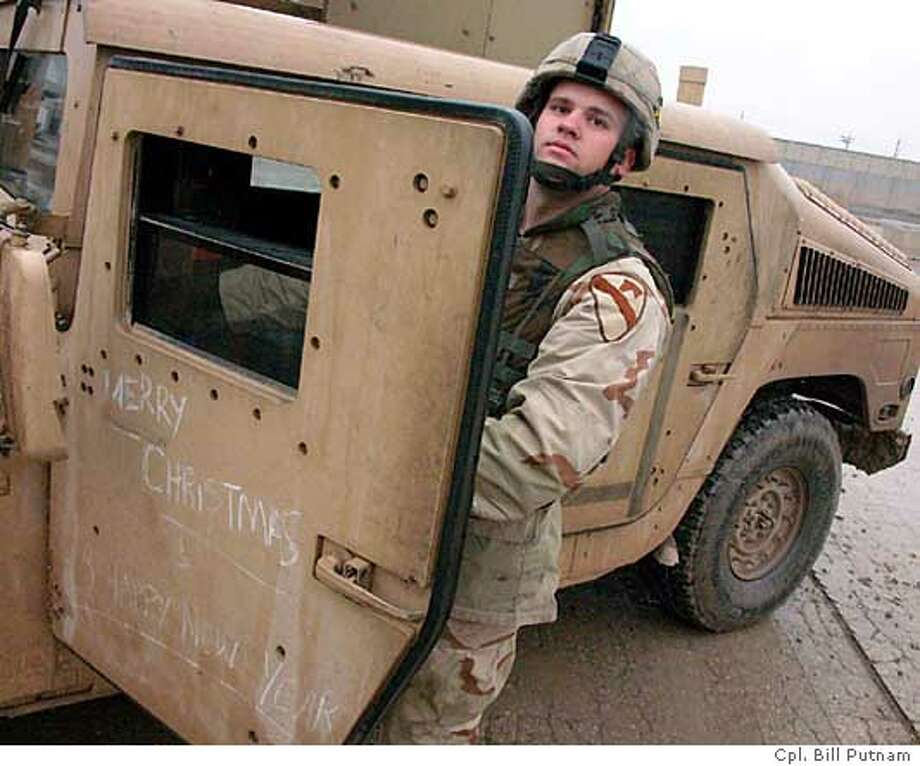 Sgt. Brandon Shaw, of the U.S. Army's 1st Cavalry Division, gets ready to go out on patrol in a decorated Humvee on Christmas Day. COURTESY CPL. BILL PUTNAM, 122ND MPAD Photo: No Name