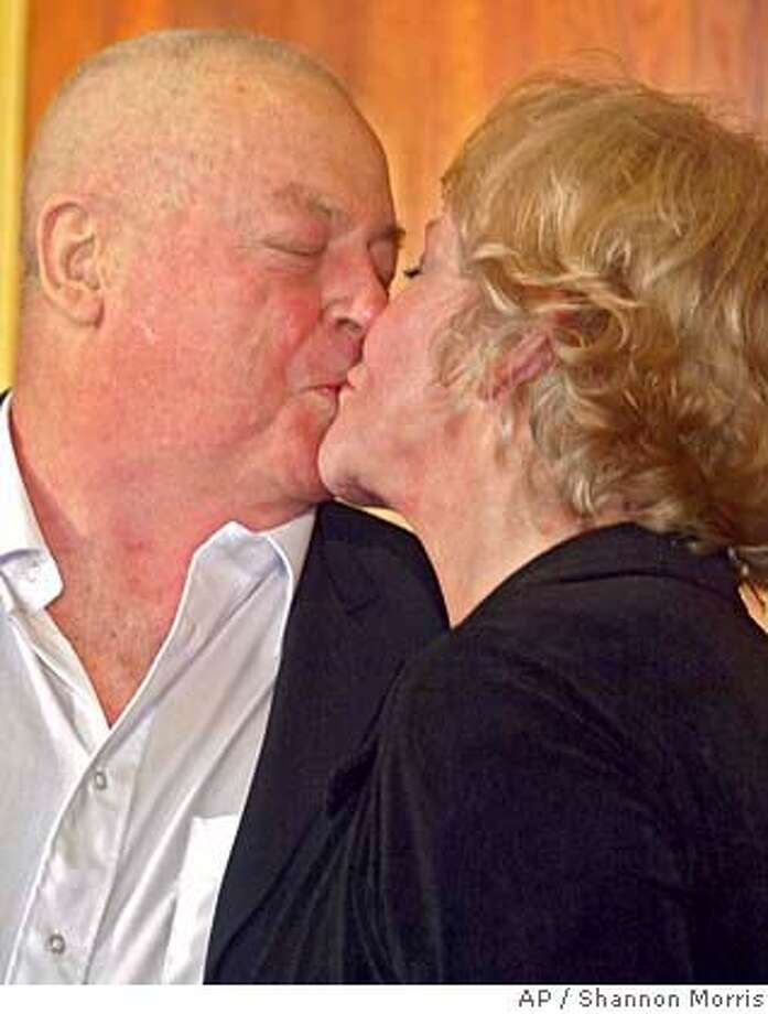 Australian engineer Douglas Wood, left, kisses his wife Yvonne Given during a press conference on his arrival back in Australia at Melbourne Airport, Monday, June 20, 2005. Wood who was dramatically rescued from insurgents in Baghdad last week said he never gave up hope during his 47-day ordeal that his family would keep trying to free him. (AP Photo/Shannon Morris) Photo: SHANNON MORRIS