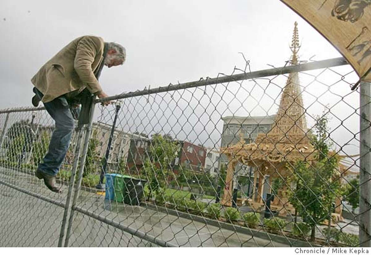 temple17015_mk.jpg David Best trys his best to get past a newly locked fence that surrounds his temple art in on Hayes Green. Larry Harry, Burning Man founder, suggested this art was ment to be lead community interaction and the fence should come down. Burning man enthusiasts and members of the Bay Area art community attend a dedication for the latest David Best temple creation recently erected on the Hayes Green in San Franicsco. 6/15/05 Mike Kepka / The Chronicle MANDATORY CREDIT FOR PHOTOG AND SF CHRONICLE/ -MAGS OUT
