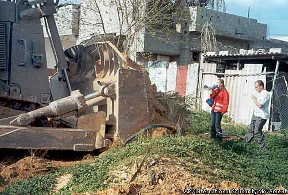 "** ONE OF SIX HANDOUT PHOTOS ** Rachel Corrie, 23, from Olympia, Wash., a member of the ""International Solidarity Movement,"" uses a loudspeaker as she stands between an Israeli buldozer and a Palestinian physician's house in the southern Gaza Strip town of Rafah Sunday, March 16, 2003. Corrie died Sunday while trying to stop a bulldozer from tearing down the physician's home. She fell in front of the machine, which ran over her and then backed up, witnesses said.(AP Photo/HO, International Solidarity Movement)"