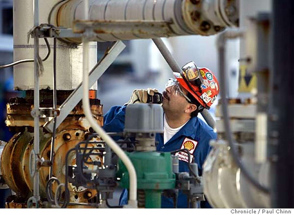 Michael Gonzalez works on a high pressure valve at the refinery. The Shell Oil Refinery on 1/12/05 in Martinez, CA. Blue collar jobs, once a mainstay of the local economy and a beacon for high school kids who knew they could always get a union job at a refinery after graduation, are a vanishing way of life in cities like Martinez . Fewer kids have any interest in following their fathers and grandfathers into the Shell refinery. PAUL CHINN/The Chronicle