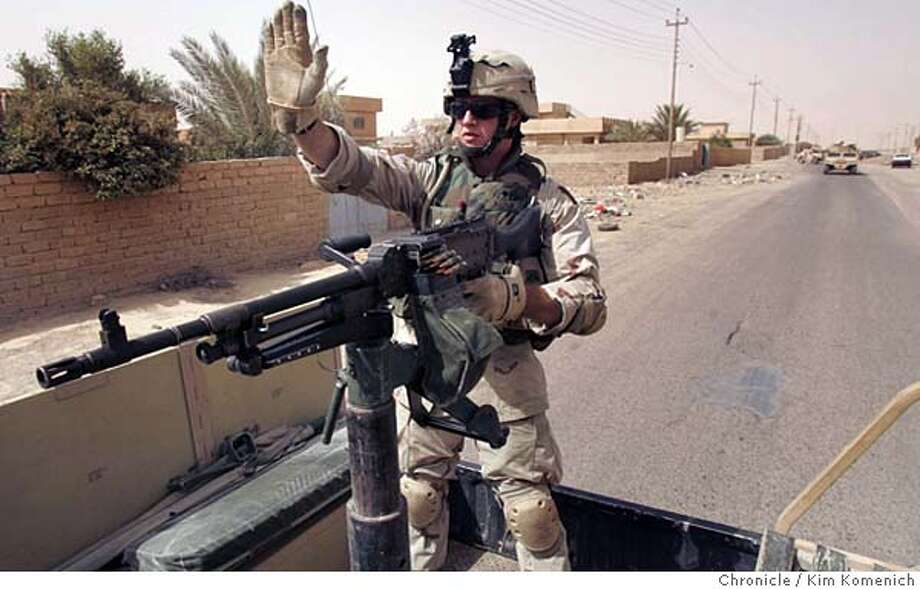 """IRAQ17_GUNNER_KK_091.jpg  Specialist Trenton Nunn of Port Allegany (cq) Penn., is the gunner on one of the four """"A"""" Company vehicles patrolling Qadessiya. He holds his hand up and points his gun at an oncoming car.  We concentrate on the role of the gunner. We go on patrol in Qadessiya and Al Hamra (north of Tikrit) with """"A"""" Company of the 1-112th Infantry Battalion (attached to the 2-7 Infantry Battalion of the First Brigade, 3rd Infantry Division.)  San Francisco Chronicle photo by Kim Komenich Photo: Kim Komenich"""