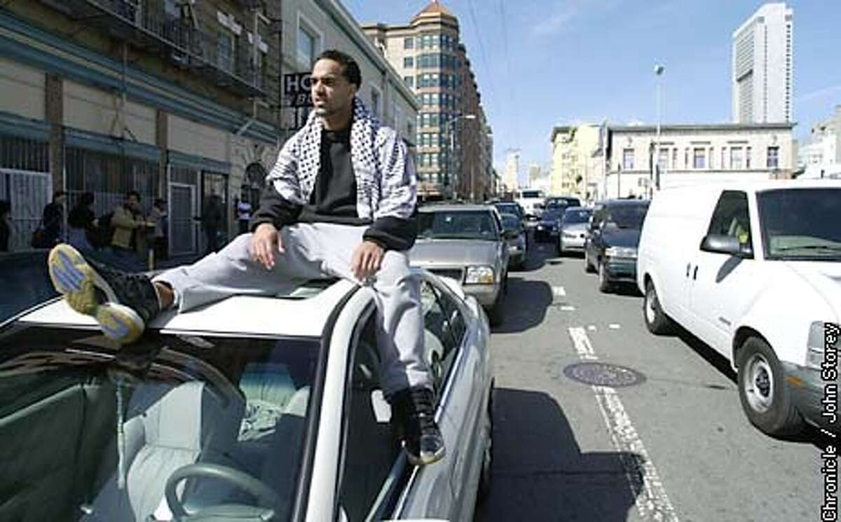 WARDEMO-C-20MAR03-MT-JRS-Demonstrations against the war in Iraq throughput San Francisco. Fady Salah of San Bruno sits on top of his car on Jones Street waits for the traffic to clear on Market Street from the protests. Chronicle photo by John Storey.