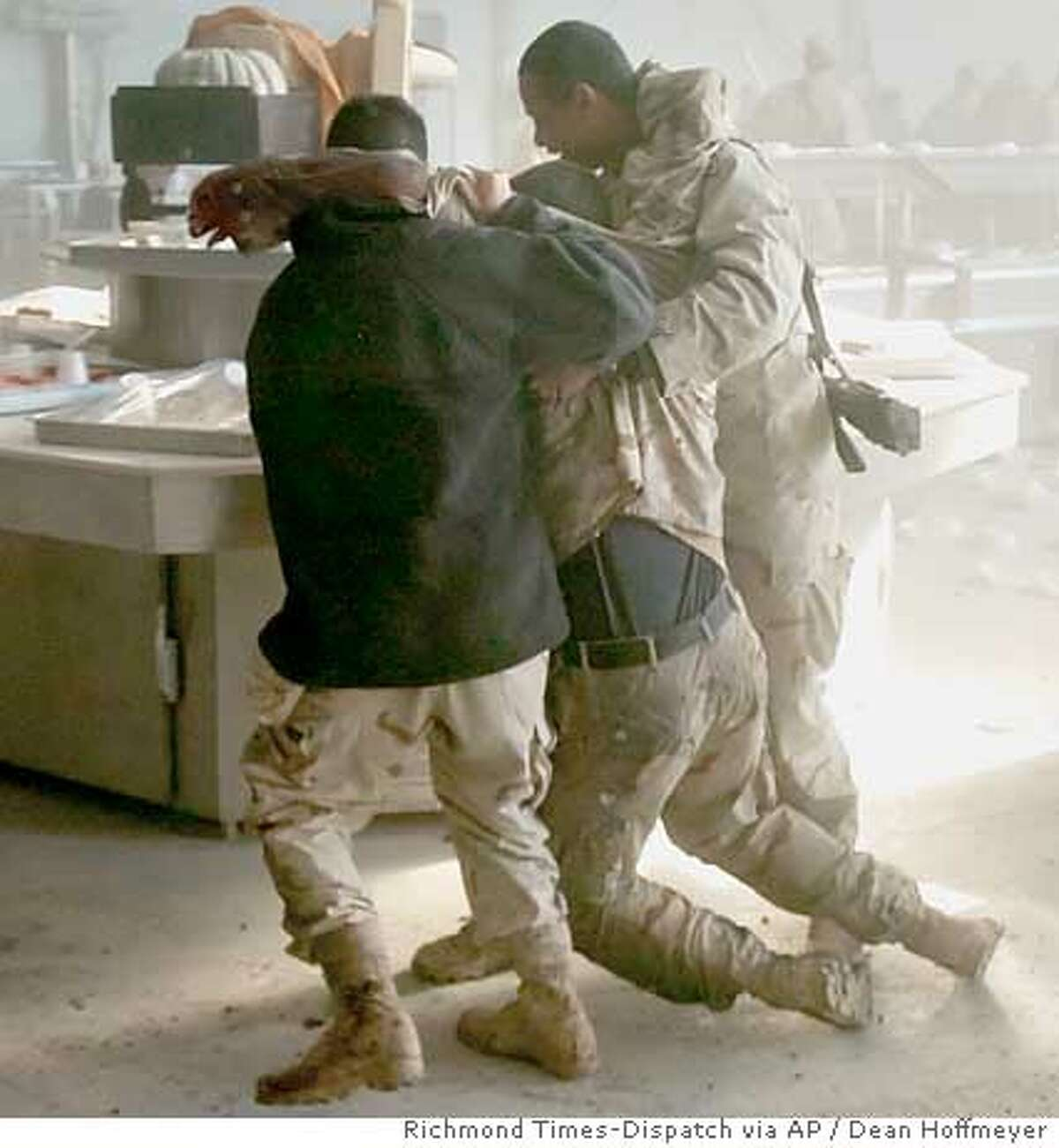 U.S. soldiers tend to the wounded after an apparent insurgent mortar attack on a dining facility during lunchtime on FOB Marez in Mosul, Iraq on Tuesday, Dec. 21, 2004. (Richmond Times-Dispatch / Dean Hoffmeyer)