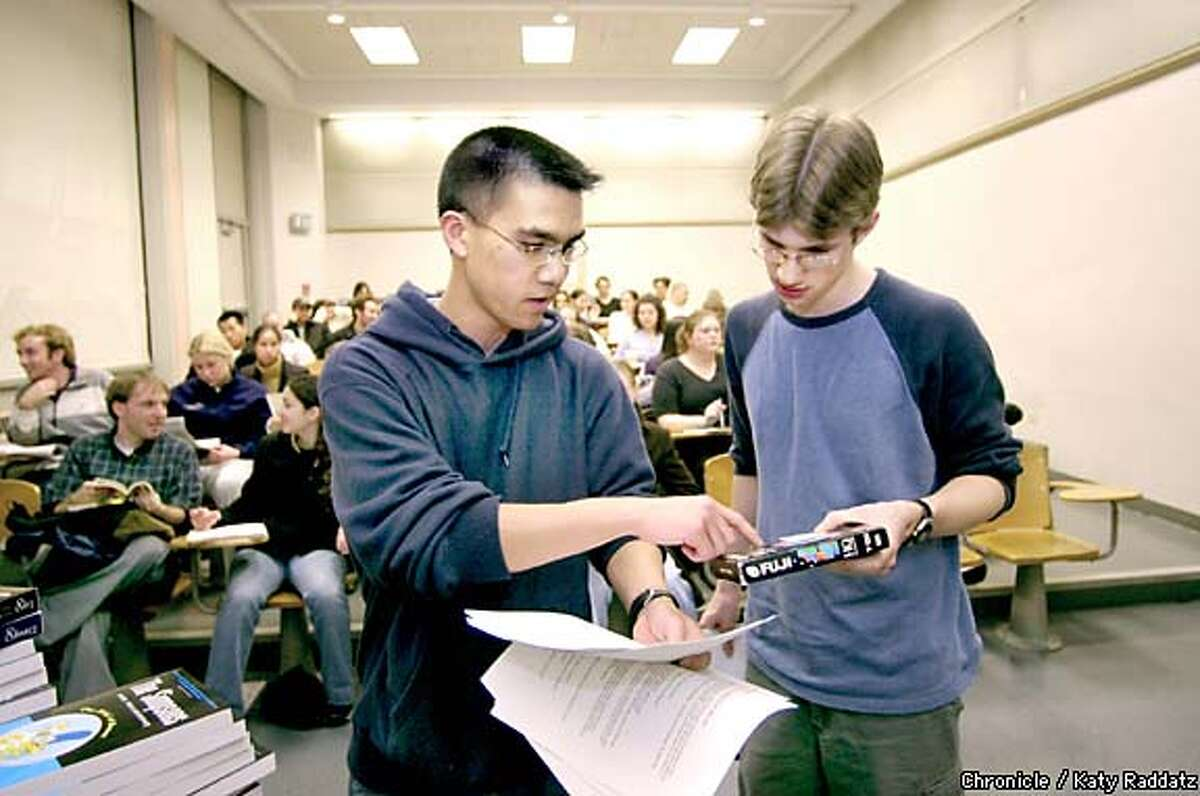 Instructor Tyler Shores, left, and student assistant Max Helix discuss the video clips they will show during a meeting of their