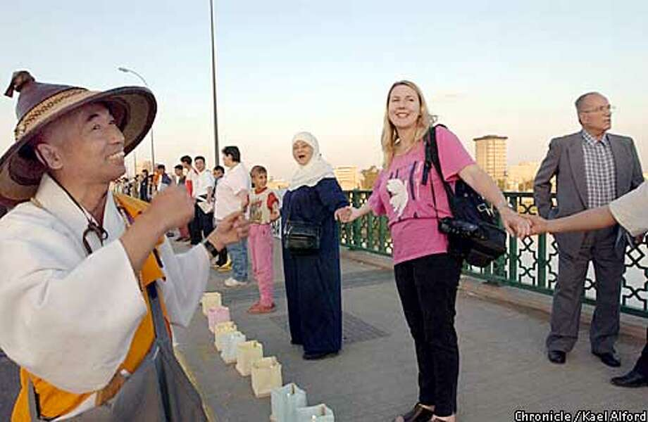 Members of the human shield volunteers participate in a candlelight peace vigil on a bridge over the Tigris river in Baghdad in the last days before an expected US-led war against Iraq. About 100 human shields spend the nights distributed at various sites expected to be primary targets of a US bombing campaign, many of which are very close to or embedded in civilian populated areas.  17 March 2003  photo: Kael Alford