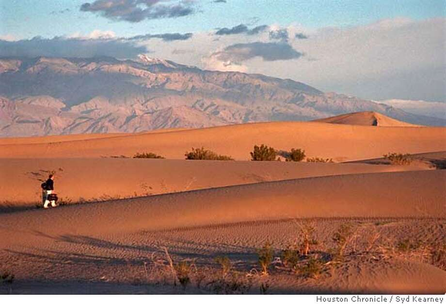(NYT9) DEATH VALLEY NATIONAL PARK, Calif. -- Oct. 1, 1998 -- DEATH-VALLEY-HNS, 10-1 -- Crossing the sand dunes in Death Valley National Park just after sunrise. Death Valley, which includes more than 3.3 million acres in California and a small part of Nevada, is becoming a year-round vacation spot. November through March are the most comfortable months for visitors, with daytime temperatures ranging from 65 to 80 degrees. Nighttime lows, accompanied by an explosion of stars, hover in the low 40s. (Syd Kearney/Houston Chronicle Photo) XNYZ HFO Photo: SYD KEARNEY