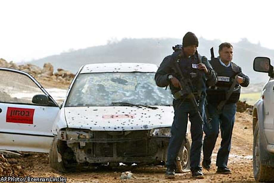 "Israeli police officers stand guard at the scene where Israeli forces backed by a helicopter gunship mistakenly shot and killed two Israelis they believed to be Palestinian gunmen, near Pnei Hever, just southeast of the West Bank town of Hebron, Wednesday, March 13, 2003. When the shooting occured, Israeli forces had been scouring the area because because of intelligence warnings that Palestinians were planning an attack in the area, the army said in a statement. The sign in the door of the car reads: ""Security Service."" (AP Photo / Brennan Linsley) Photo: BRENNAN LINSLEY"