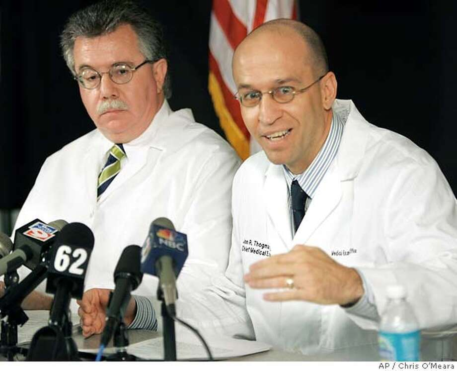 Dr. Jon Thogmartin, right, District 6 Medical Examiner, gestures as he gives a report with Dr. Stephen Nelson on Terri Schiavo's autopsy during a news conference Wednesday, June 15, 2005, in Clearwater, Fla. Schiavo's autopsy backed her husband's contention that she was in a persistent vegetative state, finding that she had massive and irreversible brain damage and was blind, the medical examiner's office said Wednesday. It also found no evidence that she was strangled or otherwise abused. (AP Photo/Chris O'Meara) Photo: CHRIS O'MEARA